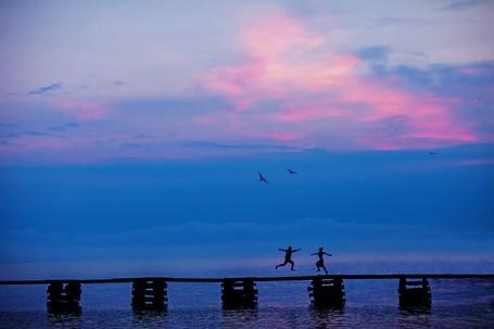 Фото Ночь на море, по мосту бегут на встречу друг к другу парень и девушка, над морем парят чайки, фотограф Илья Двояковский