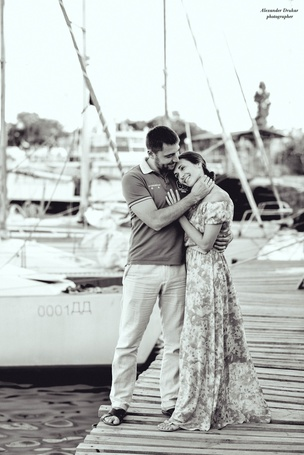 Фото Парень нежно обнял девушку, она положила голову ему на плечо, обя стоят на пирсе рядом с яхтами, фотограф Александр Друкар