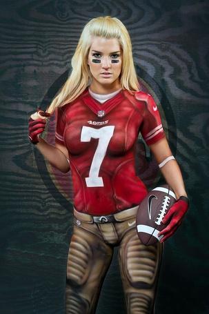 Фото Девушка с нанесенным рисунком на тело в виде формы футболистки с мячем