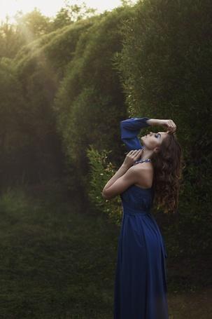 Фото Девушка - шатенка с длинными волосами в синем платье с открытым левым плечом стоит, наклонив голову назад, среди зеленых деревьев, освещенная солнцем, фотограф Иван Копченов, модель Алена Сарсарова