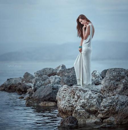 Фото Девушка - шатенка с длинными волосами, в белом платье, с голубым браслетом на руке стоит на камнях и смотрит вниз, рядом море и вдали горы, фотограф Ира Джуль, модель Анна Кушнарева