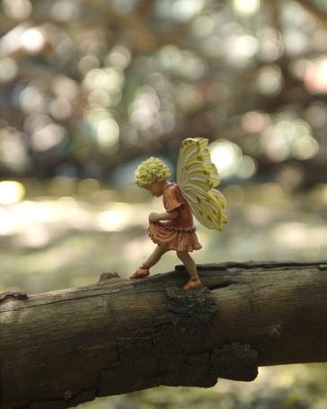 Фото Фигурка девочки-эльфа на стволе дерева