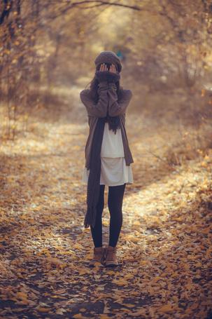 Фото Девушка стоит на дороже в лесу, закрыв лицо руками