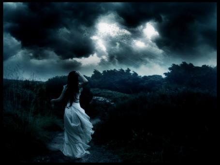 Фото Девушка стоит к нам спиной на дороге перед грозным небом