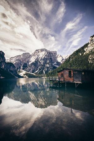 Фото Красивый пейзаж, деревянный дом стоит на берегу горного озера, в небесах плывут облака