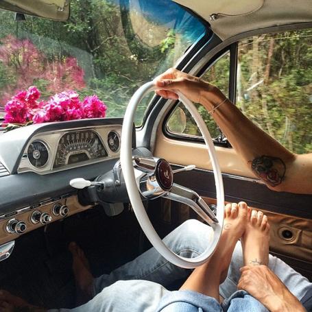 Фото Девушка положила ножки на ноги парня, который сидит за рулем авто