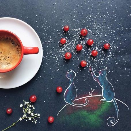 Фото Чашка кофе на блюдце стоят на столе, где нарисованы котята и лежат ягоды смородины