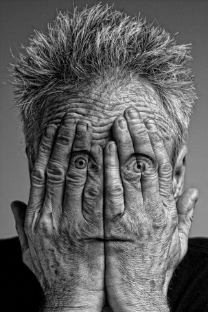 Фото Старый мужчина смотрит сквозь пальца рук, ву gerald gribbon
