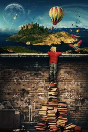 Фото Мальчик, подложив под ноги стопки книг, выглядывает с грязного, замусоренного города, через высокую кирпичную стену и смотрит на живой, полный красок и чудес другой мир