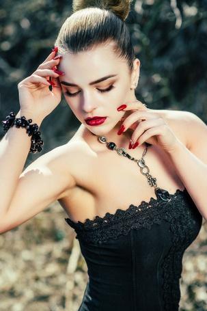 Фото Девушка с гладкой прической в черном топике с ожерельем на шее, браслетом на руке и ярким макияжем смотрит вниз, модель Катерина Громова, фотограф Юлия Денишева