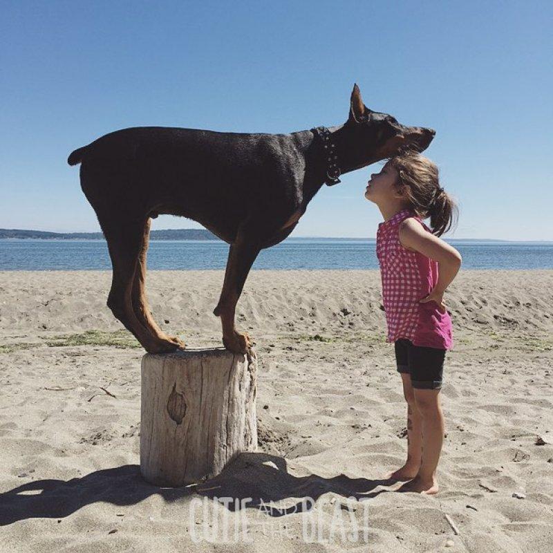 Фото Девочка с доберманом позируют на пляже на фоне моря и неба, ву Siena Prucha