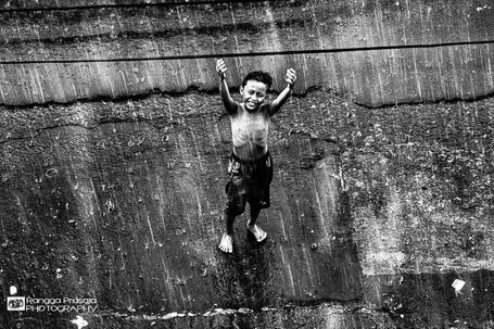 Фото Радостный мальчик, стоит на дороге, подняв руки вверх, под проливным дождем, by Rangga Prasaja
