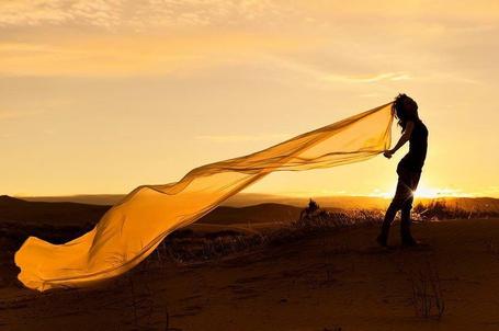 Фото Девушка с прозрачной тканью в руках стоит на фоне заката