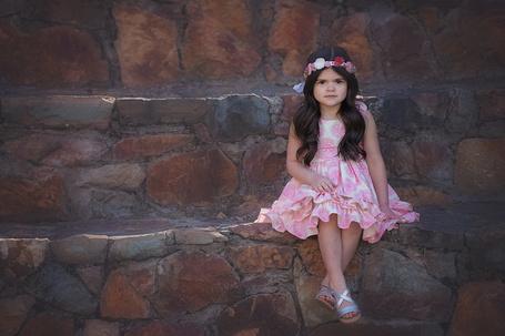 Фото Маленькая девочка с длинными, темными волосами в белом платье с узорами, с ободком в виде цветов, сидит на каменных ступеньках, by Amber Bauerle