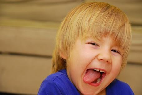 Фото Маленькая девочка на размытом фоне показывает язык