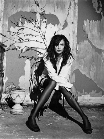 Фото Актриса Фамке Янссен / Famke Janssen, сидит на стуле, позади стены с оборванными обоями, за стулом веточка с сухими листочками, ваза с засохшими цветами и стальная птичья клетка