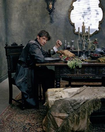 Фото Актер Хью Джекман / Hugh Jackman, с грустным взглядом сидит за накрытым столом, актер втыкает вилку в кусок жареного мяса