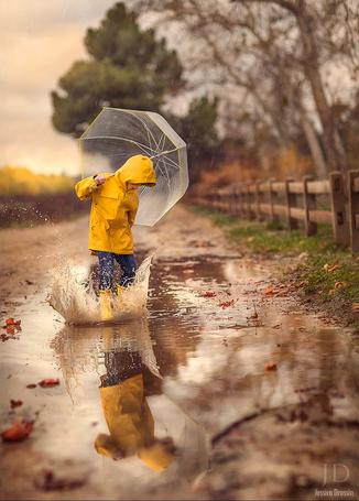 Фото Мальчик в желтом дождевике и с прозрачным зонтом шлепает по луже, by Jessica Drossin