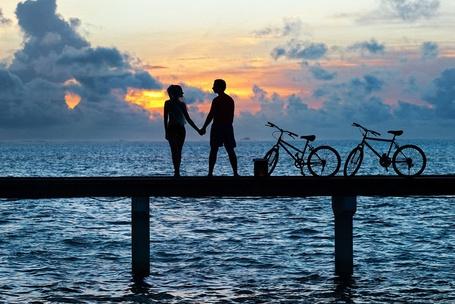 Фото Парень с девушкой и рядом велосипеды стоят на фоне облачного неба и моря