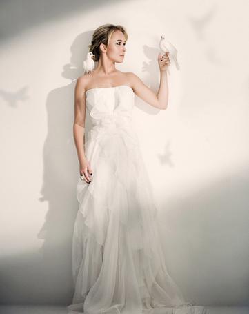 Фото Актриса Хайден Панеттьери / Hayden Panettiere, стоит в белом платье у стены с белой голубкой на плече, вторая голубка сидит у девушке на руке