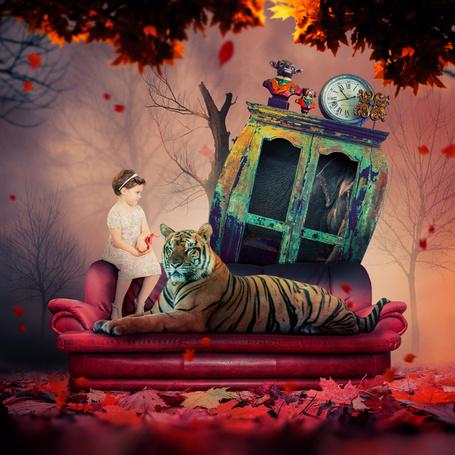 Фото Девочка сидит на диване, рядом с тигром, за диваном стоит старый шкаф со слоном