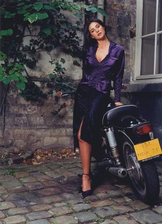 Фото Актриса Моника Беллуччи / Monica Bellucci, стоит у припаркованного у дома мотоцикла