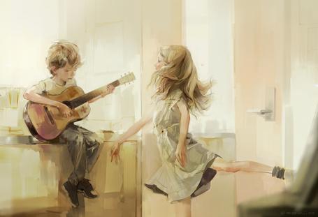 Фото Играющий на гитаре мальчик и танцующая под его музыку девочка