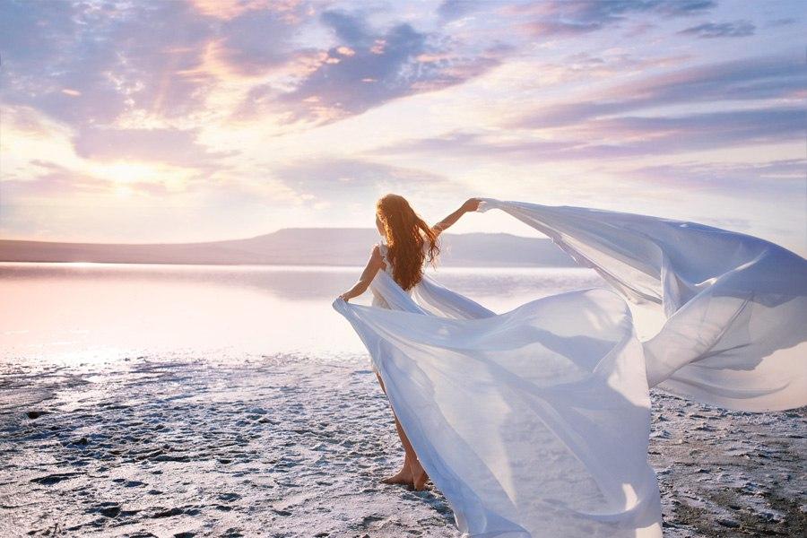 Фото Девушка в белом платье стоит спиной к нам на берегу моря, она держит в руках развевающуюся белую ткань, модель Оксана Бутовская, фотограф Софья Бузакова