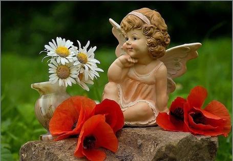 Фото Статуэтка ангелочка на камне рядом ваза с ромашками и красные цветы