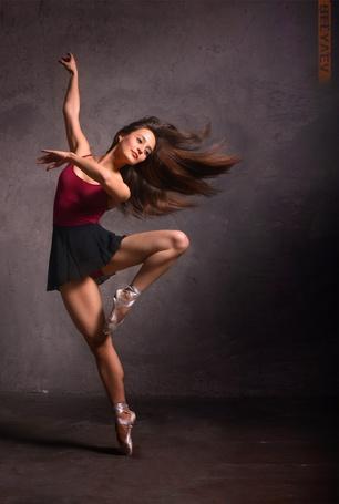 Фото Девушка шатенка в красной маечке, черной короткой юбке и в пуантах делает одно из балетных па, фотограф Дмитрий Беляев