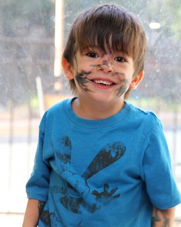 Фото Смеющийся мальчик с разрисованным лицом