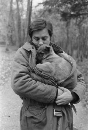 Фото Ален Делон стоит на фоне деревьев держа на руках овчарку