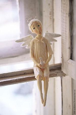 Фото Игрушечный ангел сидит на окне