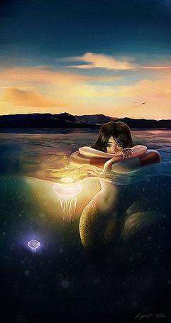Фото Русалка задумчиво облокотилась на спасательный круг, рядом плавают светящиеся медузы