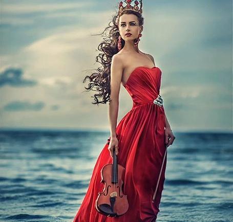 Фото Девушка в короне со скрипкой в руке стоит на фоне моря, фотограф Tatyana Nevmerzhytska