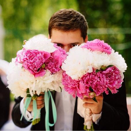 Фото Улыбающийся парень в белой рубашке и черном пиджаке с двумя букетами белых и розовых пионов смотрит на нас, фотограф Юрий Лукша