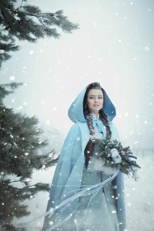 Фото Девушка в голубой накидке держит еловые ветки