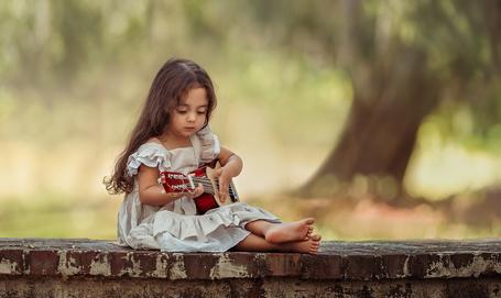 Фото Девочка сидит на бордюре и играет на гитаре