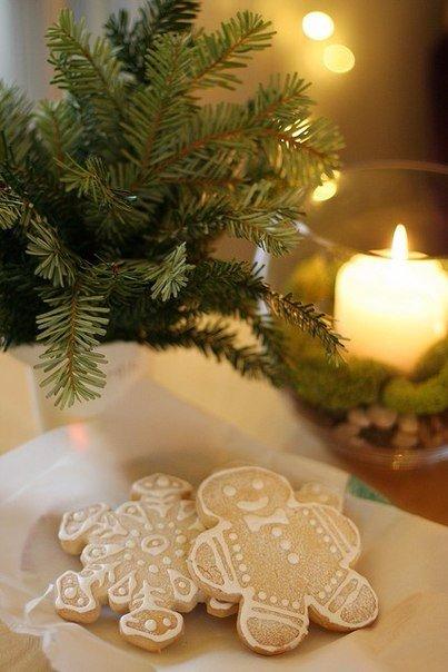 Фото На тарелке с салфеткой лежат печенюшки в виде снежинок и человечка, рядом стоят в вазе ветки хвои и горящая свеча в стеклянной чаше с украшениями, by Elena Kovyrzina