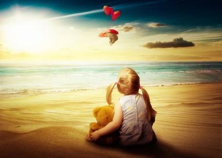 Фото Девочка с медвежонком сидит на берегу моря и смотрит на медведя, летящего на зонтике с шариками-сердечками, by Reto Imhof