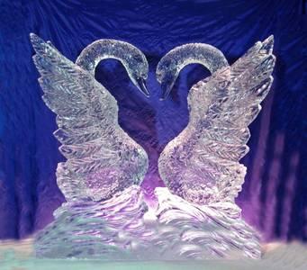 Фото Два лебедя, вырезанные из льда, стоят друг напротив друга, расправив крылья
