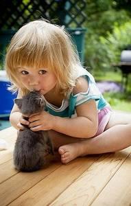 Фото Светловолосая девочка сидя на деревянном полу, с нежностью целует маленького котенка