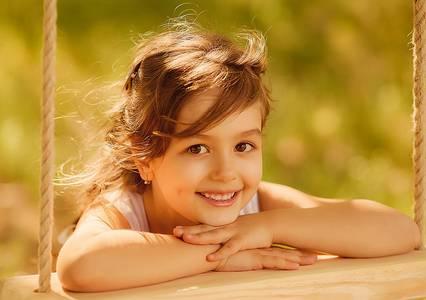 Фото Улыбающаяся девочка положила руки на деревянной доске качелей и смотрит на нас, Shepel Sanchezzz