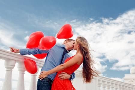 Фото Девушка в красном платье обнимает парня держащего в руке воздушные шарики