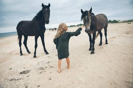 Фото Девочка на берегу моря с двумя мустангами