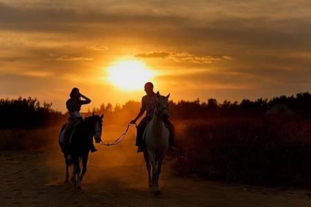 Фото Мужчина и девушка едут на лошадях, мужчина ведет за уздечку лошадь, на которой сидит девушка, фотограф Дмитрий Никитин