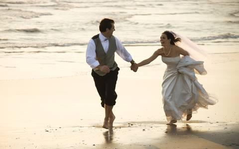 Фото Счастливые молодожены босиком бегут по берегу моря