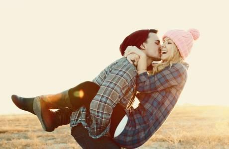 Фото Парень целует девушку в розовой шапочке, держа ее на руках