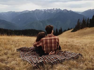 Фото Парень с девушкой сидят, обнявшись и смотрят нагоры и лес