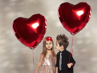 Фото Мальчик с ирокезом и девочка в блестящем платье держат воздушные шары в форме сердца